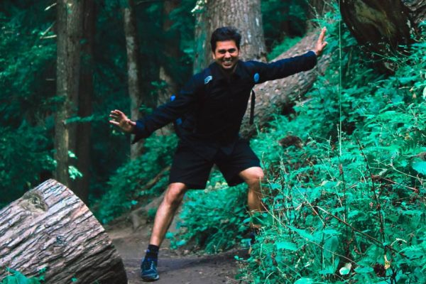 Man walking between two trees